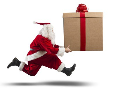 Running santa Claus with a big gift on a street